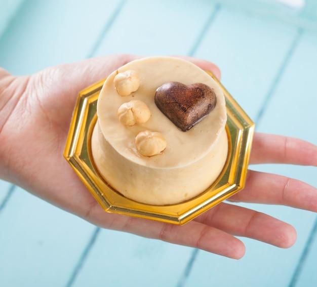 Маленький торт с фундуком в женской руке.