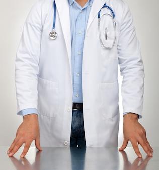 検査のためテーブルの上に休んで手を持つ医師