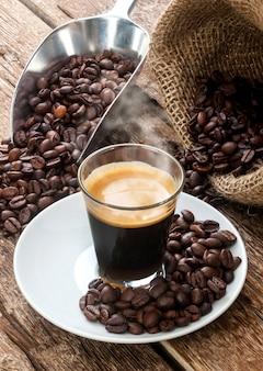 Кофе эспрессо в стеклянной чашке с кофейными зернами.