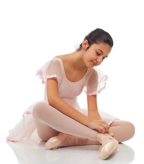 ダンスのために彼の靴を結ぶ間バレリーナ。