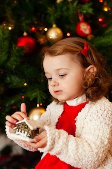 クリスマスツリーの近くの美しい小さな子供。