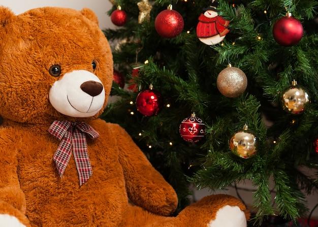 プレゼントとクリスマスツリーの近くのテディベア