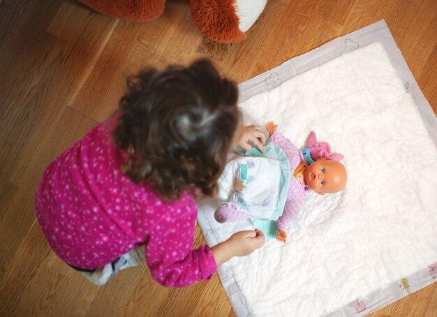 小さな女の赤ちゃんは彼女の人形のおもちゃにおむつを変更します。