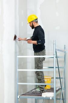 石膏ボードの壁を左官工事労働者。