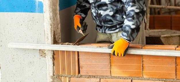 Каменщик устанавливая кирпичную кладку на внутреннюю стену.