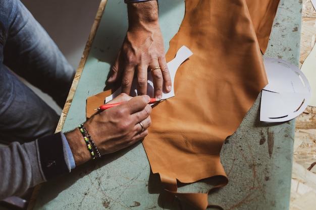 Дизайнер обуви работает с кожей.
