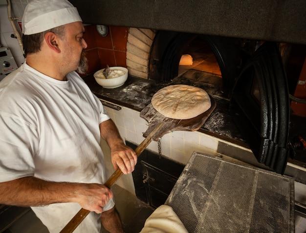 ベーカリーでの木製オーブンによる焼きたてのパンの製造。