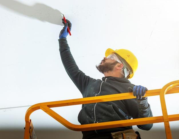 労働者は石膏ボードの壁を構築します。