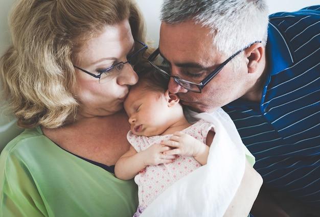 眠っている生まれたばかりの赤ちゃんの孫娘を保持している祖父母