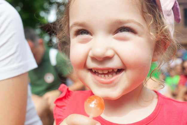 Маленькая девочка держит в руке леденец
