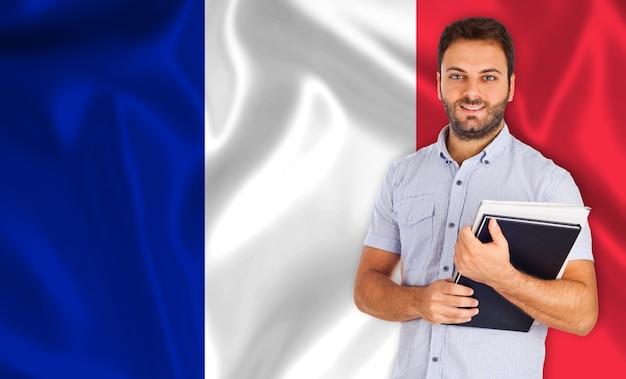 フランスの旗の上の男子学生