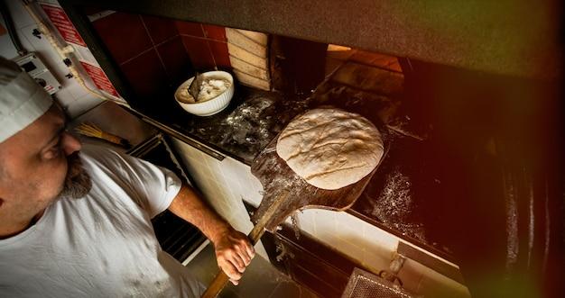 ベーカリーでの木製オーブンによる焼きたてのパンの製造