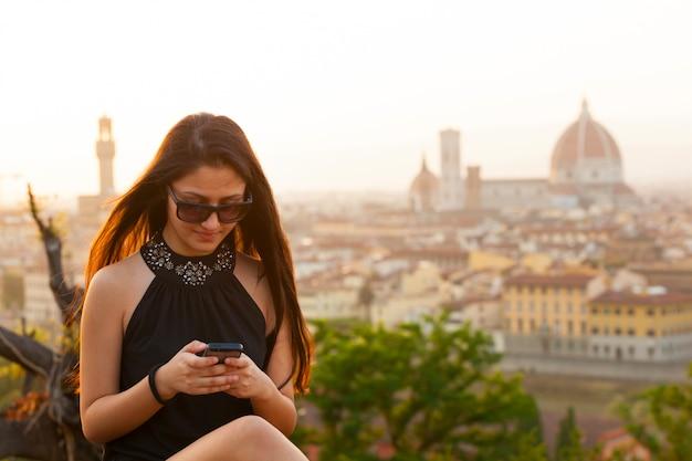 フィレンツェの夕暮れ時のティーンはスマートフォンを使用