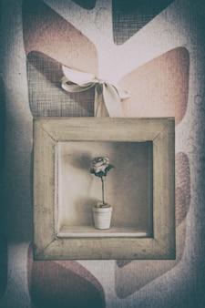 Маленькая ваза с розой внутри маленькой картинной рамки.