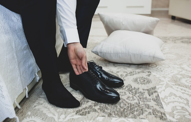 スーツを着た男は、黒の古典的なエレガントな靴の靴ひもを結びます。