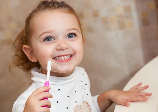 Милый зуб чистки маленькой девочки с щеткой.