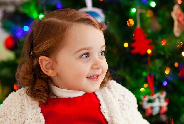 クリスマスツリーの近くの美しい小さな子。