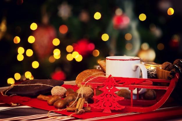 クリスマスツリーの後ろに熱いお茶のカップ。