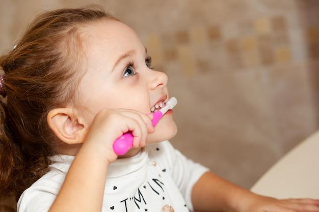 かわいい女の子がブラシで歯をクリーニングします。