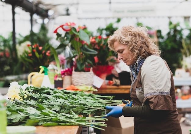 Флорист с профессиональной одеждой в магазине