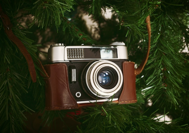 人工のクリスマスツリーに掛かっているビンテージカメラ