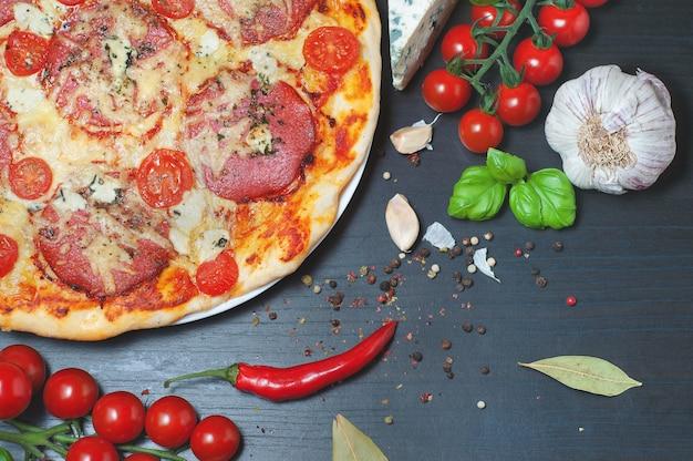 ピザと野菜の暗い木製のテーブル。黒い背景にピザのための原料。