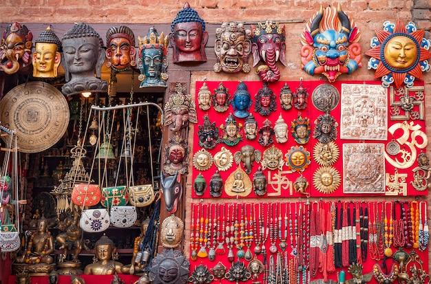 ネパール、カトマンズのタメル地区の伝統的な市場でカラフルな彫刻が施された木製のマスクと手工芸品