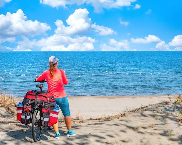 Молодая женщина турист на горном велосипеде с большим рюкзаком путешествует по побережью черного моря