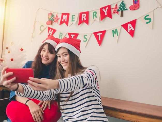 Две женщины азии, улыбаясь, фотографируют в рождественской вечеринке