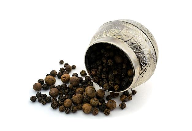 Специи перец черный горошек посыпать рядом с винтажной металлической посудой