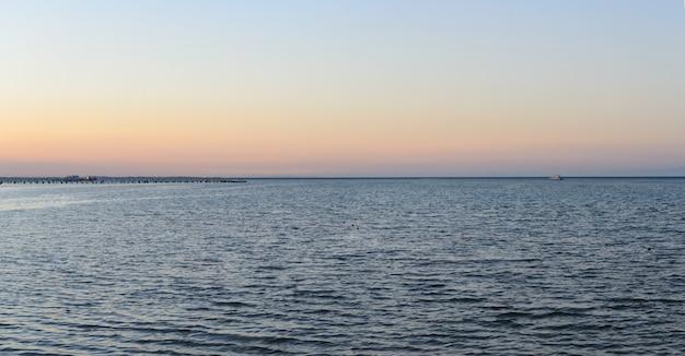 地平線と夕方のパノラマの桟橋の海岸ヨット