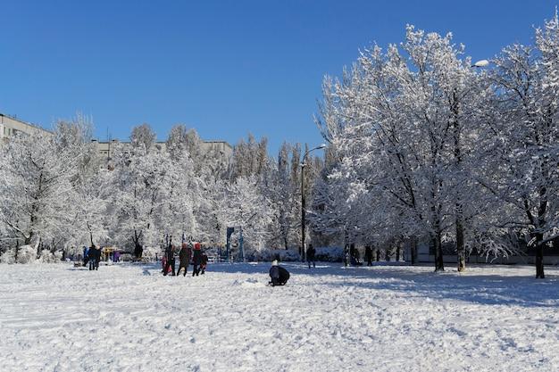 Зимний пейзаж, детская площадка, город в чистом снегу играют дети