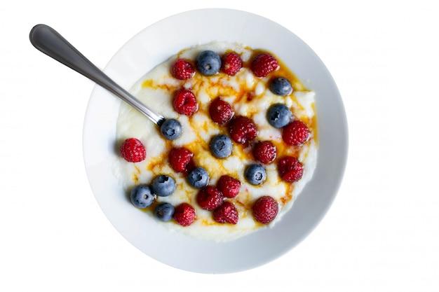ラズベリーとブルーベリーを白で隔離される健康的な朝食セモリナ