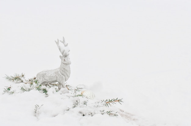 白い雪でシルバーグレーの光沢のあるクリスマスのトナカイ