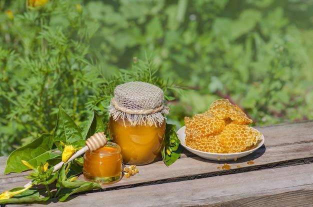 素朴な木製のテーブルの上の蜂蜜ディッパーと瓶の中の蜂蜜
