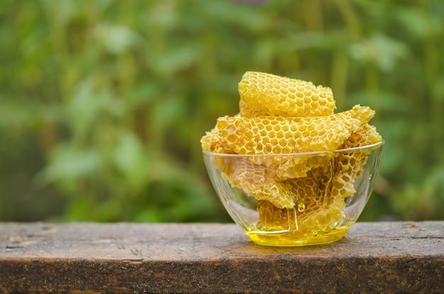 新鮮なハニカムと蜂蜜をボウルに入れます。有機天然成分レタリングスペース