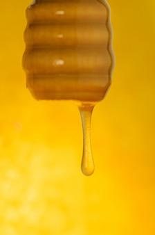Поток меда течет. поток льется медом. мед течет из деревянной ложки