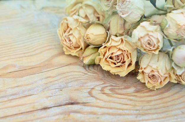 木製の背景に枯れたバラ