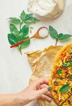 ピザのスライスを取って手。スライスピザを持っている手。