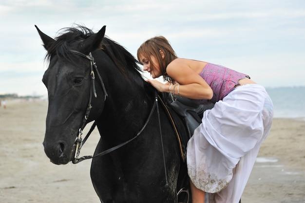 女性はビーチで馬に乗る