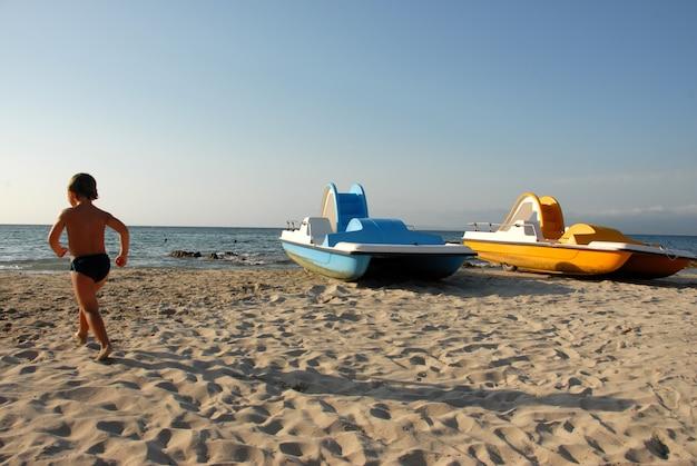 Пляж, мальчик и водные велосипеды