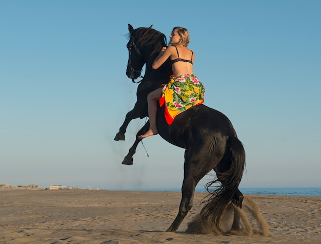 馬の女性と彼女の黒い種馬のビーチでの飼育