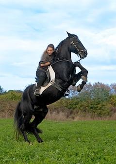 Езда девушка и черный жеребец