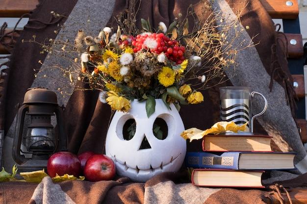 オイルランプ、リンゴ、ジャックの形の花と茶色のカーテンに対する本と花瓶のある静物構成