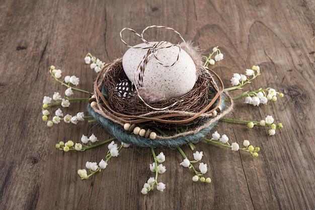 卵と春の花とオークのテーブルに装飾的なイースターネスト