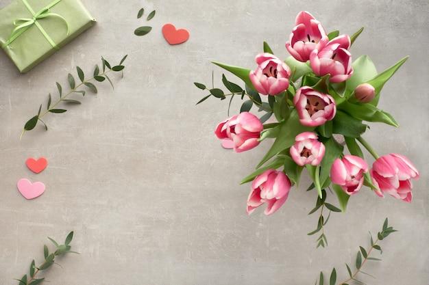 ピンクのチューリップ、ユーカリの葉、石のギフトボックスの束と春フラットレイアウト