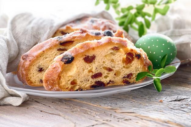 イースターのパン、新鮮な葉と塗られた卵の素朴な木の伝統的なフルーティーなパンのクローズアップ
