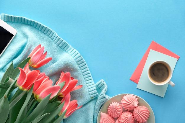 ミント色の綿のセーターとグリーティングカードにピンクのチューリップ