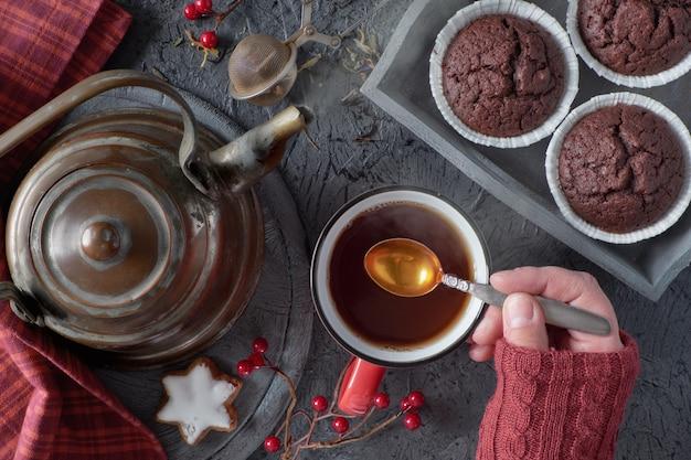 秋の寒い朝に女性の手がスプーンでお茶をミックスします。