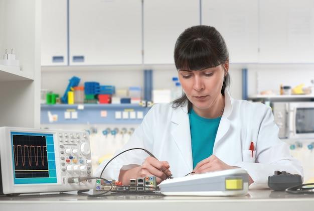 若い女性技術者またはエンジニアが研究施設の電子機器を修理